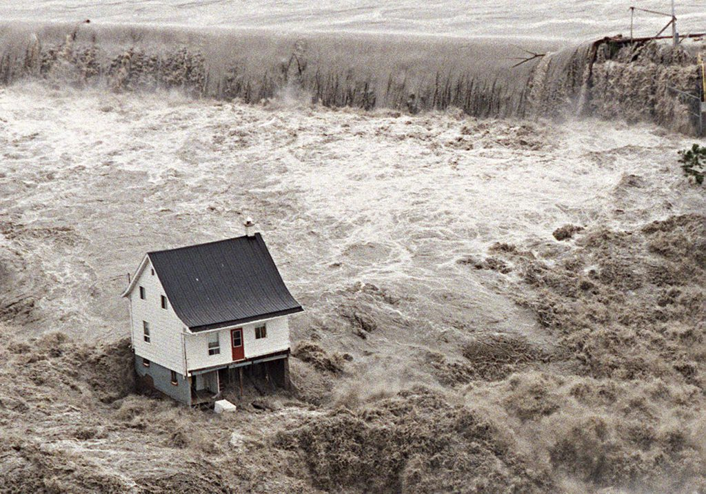 An aerial view of an overflooded dam on the Chicoutimi river July 21, 1996; shows a house resisting a major flood in downtown Chicoutimi.Victims of current catastrophes in Canada could spend years battling the painful, psychological effects of losing their wordly possessions, according to post-disaster research. Mental health experts warn that the aftermath of natural disasters - like major floods and fires - can inflict deep, long-lasting psychological injuries for victims. THE CANADIAN PRESS/Jacques Boissinot